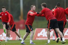 England captain Rooney (left) stretches off with fellow international Michael Carrick at the Tuesday morning training session