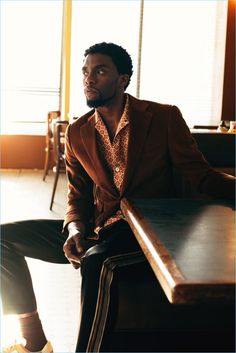 Actor Chadwick Boseman sports a Thom Sweeney corduroy suit jacket and Prada shirt. Boseman also wears CMMN SWDN satin sweatpants and Paul Smith sneakers.