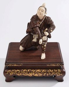 A Japanese ivory and hardwood okimono: of a kneeling samurai warrior adjusting his armour, mounted on a hardwood and gilt decorated rectangular stand, total height 20cm.