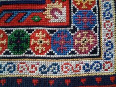 Table Runner. Cross stitch worked on red 18-count Aida evenweave fabric, based on an oriental rug design. Detail of corner.