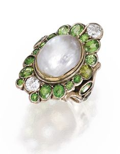 GOLD, NATURAL PEARL, DEMANTOID GARNET AND DIAMOND RING. Centered by a natural pearl measuring approximately 13.7 by 9.9 mm, framed and flanked by 23 round and oval-shaped demantoid garnets weighing approximately 3.75 carats, further set with two old European-cut diamonds weighing approximately .60 carat