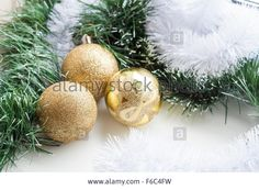 Download this stock image: Gold decorative Christmas ball and green and white garland on white background - F6C4FW from Alamy's library of millions of high resolution stock photos, illustrations and vectors.