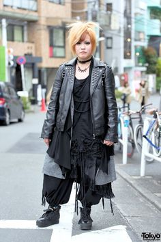 Kurumi, 19 is wearing a studded leather jacket that she bought mailorder over a Sex Pot Revenge top, layered gothic bottoms that she picked up on Takeshita Dori, and studded platform sneakers with eyeball socks. Accessories – some of which came from Thank-You Mart – a spike necklace, a leather choker, and a studded Monomania backpack decorated with a large eyeball pouch. She likes the Japanese bands GazettE and Codomo Dragon, Kurumi and is a fan of the fashion brands Monomania and Sex Pot…