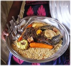 Thiéboudiène (also spelled ceebu jen, for English-speakers pronounced as chebu jen )here the iconic Senegalese fish rice pilaf garnished with whole vegetables and fish shown with a pale rice pilaf in contrast to the Thiéboudiène Boukhonk with a red rice pilaf. Gorgeous African ethnic meals, ethnic food from traditional African food and African cuisine at J'vois nice Africa! Robust, nutritionally complex, well-balanced meals.