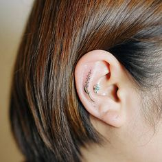 Tiny lavender tattoo on the right ear.