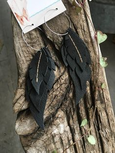 Handcrafted leather dangly earrings. Each feather is individually cut and sewn by me. They hang on stainless steel hoops and are approximately 4.25 long including the hoop. Hoops are hypoallergenic stainless steel. The delicate layers are all raven black with light brown stitching.