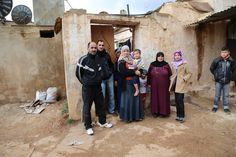 Fadia, in purple, stands with her family outside her humble home in the town of Maskaneh, near Homs in western Syria. Two years ago Fadia lived here with just two children. Her other children and grandchildren lived in Homs. But when intense fighting reached the city, they fled and now they live with her in Maskaneh. (Copyright: WFP/Dina Elkassaby)