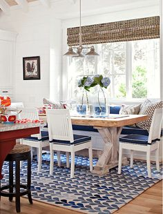 A table made from a piece of reclaimed wood creates a striking style statement in this sunny breakfast nook. The built-in banquette and dining chairs provide plenty of seating for a crowd. Accents of blue, such as on the seat cushions and the patterned Sweet Home, Dining Nook, Dining Table, Banquette Table, Table Bench, Dining Decor, White Rooms, White Walls, White Rug