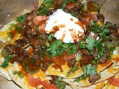 Taco Sausage, Tomato, Cilantro, Scallions, Jalapenos, Cheddar Cheese, and Greek Yogurt,  Pico Pica Hot Sauce on Tortilla Chips.