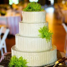 A fluted pattern gave the simple, white cake a modern edge. A few green spider mums tied the look into the guest tables.