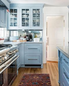 Charming cornflower blue kitchen features a red and blue rug placed in front of a stainless steel dual range positioned under a blue hood.