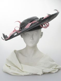 Asymmetric brim hat (front view) | Label: Judy Bentinck | Dark grey and pink sinamay and 'windowpane' large sloping picture hat. Summer wear | Made in England