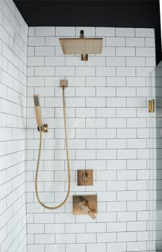 Contemporary walk-in shower features a square brass shower head paired with brass sprayer and shower kit mounted on white subway tiles framed by black walls.
