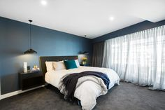 Master bedroom with blue feature wall and pops of blue in the decor. See more photos from this bedroom >>>