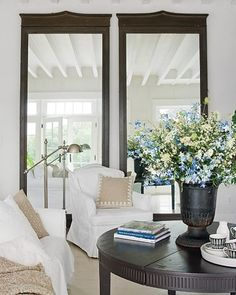 Mirrors make the room look so big & bright! Beautiful flowers & comfy chairs too :)