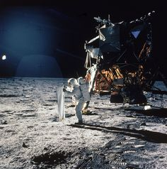 """During Apollo 11's historic moon mission in July 1969, astronaut Buzz Aldrin unfurls a """"solar wind sheet"""" designed to collect atomic particles blowing from the distant sun. The Lunar Excursion Module, which got Aldrin and Neil Armstrong safely to and from the lunar surface, stands behind him. (see more photos here)"""
