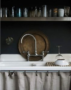 ...the nostalgia of farmhouse sink...eclectic collection of jewel tone glasses...well loved wooden tray...i want to see the rest of the kitchen! :-)