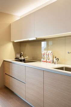 Handle-less cabinet doors and a compact hob hood concealed under the cabinet help to maintain a sleek, modern look