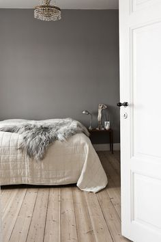 gray walls, fur blanket, light wood