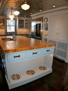 Dogs can dine in style with built-in dog bowls at the base of a kitchen island designed by Artisan Kitchens Inc. in Osterville, Mass. Drawers with dog bone cutouts conceal pet food and treats.