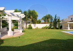 Ao lado da piscina, um belo pergolado em alvenaria oferece um espaço charmoso em meio ao jardim cuidado por paisagistas.