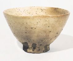 A HAGI CHAWAN [TEABOWL]   Momoyama/Early Edo Period (Early 17th Century)   With tall foot, warped mouth, splayed sides and irregularly shaped rim, the exterior with a creamy, finely crackled glaze running down over the foot ring, the interior with a lighter-coloured glaze, both over an orange and dark grey body.