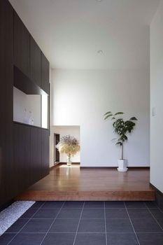 シンプルだが主張のある玄関。印象的なのが、空間を凹ませたギャラリースペース。フィックスの窓から光を採りこみ、印象に残る空間デザインが完成した。クローゼットは下部に間接照明を埋め込み浮遊感を漂わせ、ホールは濃いグレーのタイルを、フローリングはブラックチェリー材を使い、落ち着きのある佇まいとなった