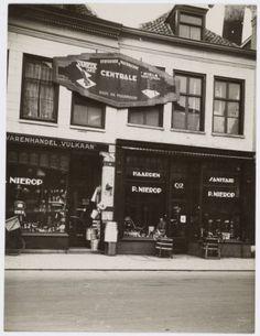 """De winkels van P. Nierop aan de Langestraat 90 en 92. Oorspronkelijk bijschrift van Bureau Gemeentewerken: """"Ontsierende reclame""""."""