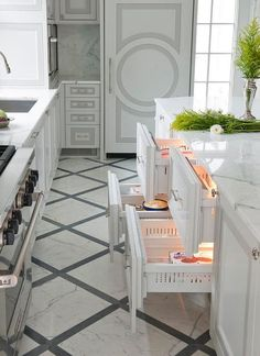 White and gray diamond pattern floor tiles frame a white two tone white and gray center island fitted with a polished statuary marble countertop and hidden paneled fridge drawers with polished nickel pulls.