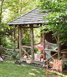 This backyard garden shed offers extra outdoor living space, courtesy of a porch strung with a Pawleys Island hammock. The lanterns and cushions are by Pottery Barn.