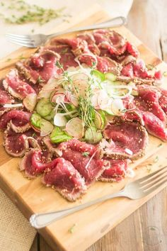 A serving of beef tataki with cucumber and radish salad served on a wooden board with a fork in the foreground