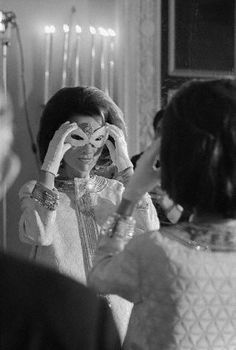 Princess Lee Radizwell, sister of Mrs. John F. Kennedy, wife of the late President, adjusts her mask after arrival at a masked ball thrown by best-selling author Truman Capote. The rich, celebrated, beautiful and social of two continents were invited to the socially historic ball. — Image by © Bettmann/CORBIS