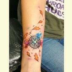 das ist eine idee für eine schöne bunte tätowierung mit orangen blättern und einem schwarzen kompass   eine hand mit compass tattoo
