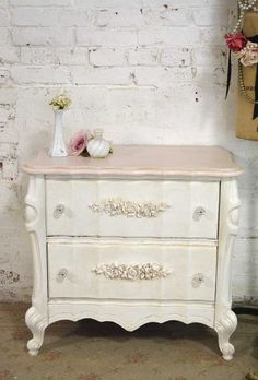 A beautiful pair of French night tables for your romantic home! FEATURES: Very sturdy solid wood construction. Two dovetail drawers with appliqués and glass knobs. FINISH: Painted with our cottage pink and tea-stain distressed just right. MEASURES: 21.5 L X 16 D X 24H PERFECT FOR YOUR: Shabby Cottage , Beach House, Farmhouse or Paris Apartment This is a vintage one of a kind piece. We carefully inspect these pieces. Each piece is hand painted and distressed. There are some nics and chip...