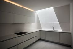 Kitchen with clean lines and daylight inside the House on a cliffside by Fran Silvestre.