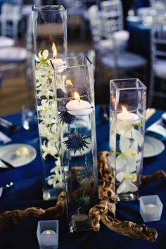 I like these tall glasses with flowers submerged and candles on top.