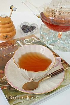 Tea:  Lavender tea in a plain china teacup with saucer, with a spoon, a beehive honey pot, and a tea magazine.