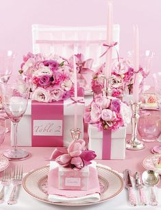 pink & gift boxes pink tablescape elegant formal dining, pink theme candles and bouquet raised on gift boxes table numbers for height in centerpiece flower arrangements