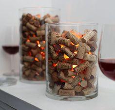 As rolhas das garrafas de vinho podem ser usadas para montar uma inusitada luminária. Coloque a vela protegida por um copo de vidro dentro de um recipiente maior e preencha com rolhas.