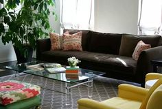 Brown sofa with glass table, white walls and mustard red green complementary colours