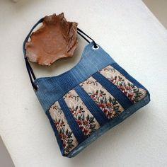 Džíska gobelínka 2 Kabelka je ušita z recydžínoviny středně modré barvy. Přední strana je ozdobená vsadkami fragmentů gobelínu s květinovým motivem. Kabelka je důkladně podlepená, dobře drží tvar, je uzavíratelná na pevný zip, Pevná tmavomodrá podšívka má 4 kapsy z původních džín Výška v nejnižším bodě 24 cm, horní šířka 30 cm. Pevné dno má rozměr 6,5 ...