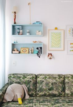 Nichos azul claro, composição de quadros e sofá com estampa tropical nesse quarto infantil.