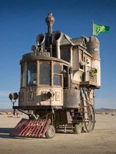 """Shannon O'Hare of Vallejo, Calif., took the frame of a fifth-wheel camping trailer and built a three-story Victorian mansion on top. The powertrain for the motorhome is from an 80-year-old forklift three-cylinder motor driving a hydraulic pump that in turn powers a wheel motor connected to an International pickup truck axle. The driver steers the front-drive machine from a command deck in the front of the vehicle via hydraulic cylinders.  The first floor of the mansion is the """"engine room""""…"""