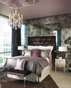An Urban Glam bedroom featuring an acid-etched mirror wall, tufted purple velvet headboard, and crystal chandelier, for an interesting mix of city and romance  (via RSVP Design Services)
