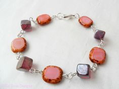 This pink bead bracelet is handmade using creamy pink lozenge shaped beads with mottled edges, and alternating dark pink glass cubes. The bracelet measures cm from end to end and fastens with a silver-plated trigger clasp. Brighton Shops, Glass Cube, Rose Design, Organza Bags, Silver Plate, Jewerly, Plating, Artisan, Beaded Bracelets