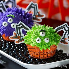 """These spooky-cute spider cupcakes look awesome on a tray of black mini gumballs. Click to get the how-to for creating bright Halloween icing tints and funny faces. """"Boo""""-appetit!"""