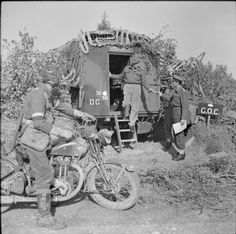 A motorcycle despatch rider watches as the message he has brought to 8th Indian Division HQ is handed to the GOC, Major General D Russell, b...