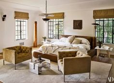 Brent and Berkus's RH bed, dressed in Matteo linens, is flanked by 1970s Italian tables. The circa-1960 chairs wear an Edelman Leather suede. Circa-1950 French bronze saucer light; custom Roman shades by The Shade Store; Maria Pergay steel table; HD Buttercup rug.
