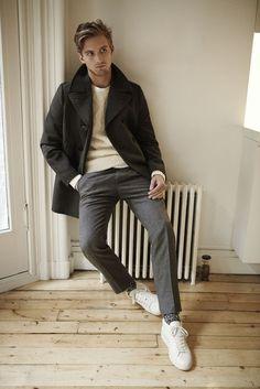 Lässiges Outfit aus anthrazitfarbenem Peacoat, schlankgeschnittener, grauer Flanellhose, beigefarbenem Strickpullover mit Zopfmuster und weißen Sneakers.