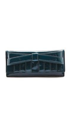 A lustrous patent leather bow and logo plate detail this faux leather wallet sleeve, which is outfitted with a zip pocket. The interior includes 6 card slots. Dust bag included. @Shopbop